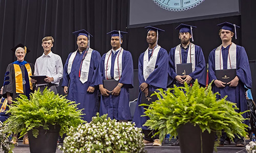 Jordan McNair's classmates and President Kolovani on stage at Commencement.