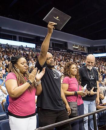 Jordan McNair's parents, (center) Dexter McNair and Paula Borchert, accept his certificate during a standing ovation from classmates.