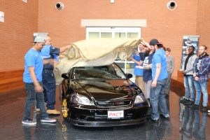 The restored Honda is unveiled to family and friends at the college's Regional Automotive Center.