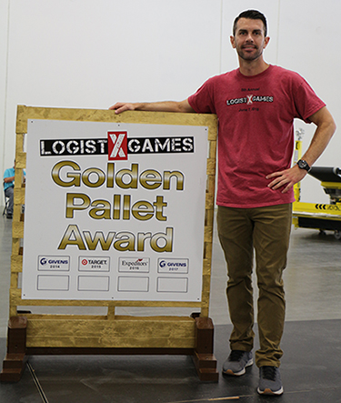 "Kevin Hughes, Suffolk's director of economic development, standing next to the ""Golden Pallet Award"" at the Hampton Roads LogistXGames."