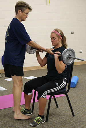 Student Denise Brown shows a fellow classmate how to properly lift.