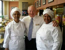 Mayor Paul Fraim poses with Brandy Reid, left and Jaquana Branch, two spring 2010 graduates.