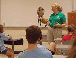 Margie Gomez shows off a red-tailed hawk.