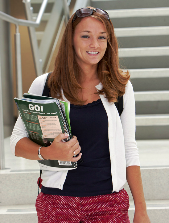 Female student walking with books in hand