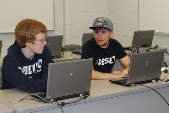 Timothy Collins and Travis Barnes share ideas in class.