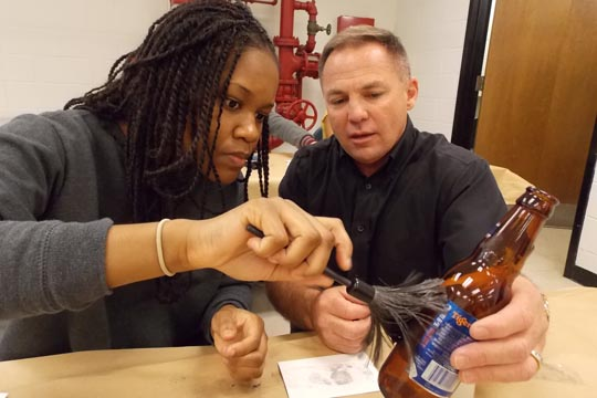 Diamon Stephens works the Don Haley, program head at the Virginia Beach Campus during a fingerprinting exercise