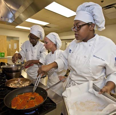 culinary students work around a stove