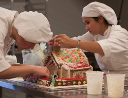Two culinary students decorate a gingerbread house