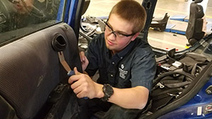 Student repairing the inside of a car door