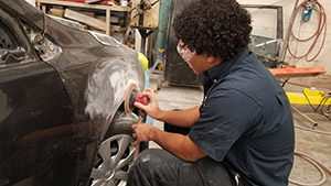 Student working on the outside of a car body