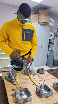 Student in safety goggles working on wiring
