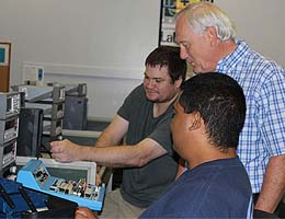 Students Michael DiMartino and Keven Perez work with professor Al Koon during a lab.