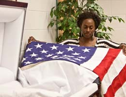 A student practices placing an American flag on a casket