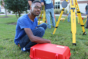 Student sits near land surveying equipment