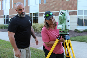 Two students work together with land surveying equipment