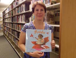 TCC librarian with a book to be sent to Guatemala