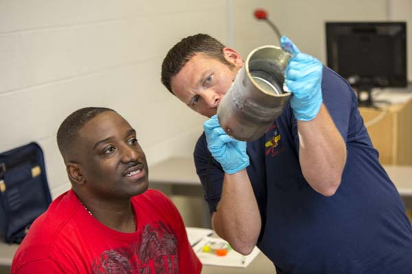 Chad Williamson showing classmate Willie Dixon a resultant defect found in a weld on a test piece used during a dye penetrant test demonstration