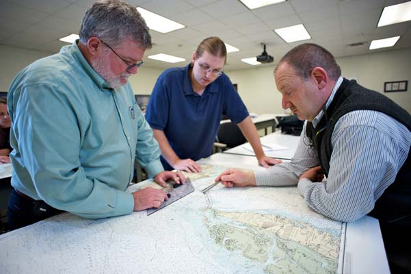 Instructor Stan Gold (right) teaches navigation skills to students at the Maritime Training Program at the Virginia Beach Campus