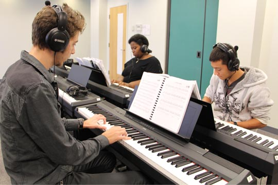 Students practice in the new piano lab on the Norfolk Campus