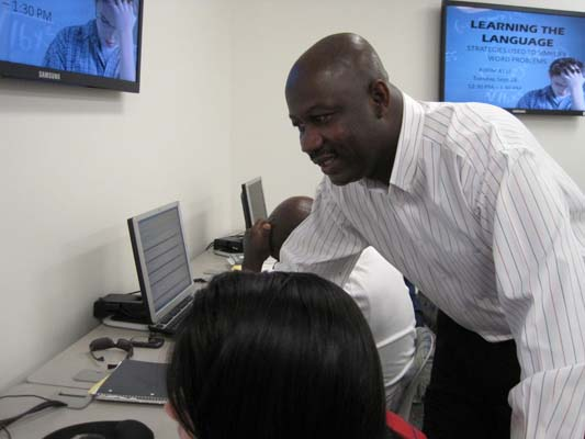 Math professor Peter Agbakpe helps a student at a computer