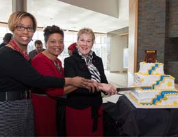 Provost Woodhouse, Student Center Director Katina Barnes and President Baehre-Kolovani prepare to cut the cake after the dedication ceremony.