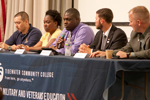 A panel of five veteran students sit at a table