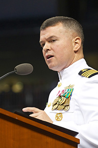 man in naval uniform speaking at podium