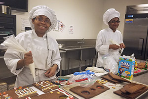 two culinary students working on gingerbread houses