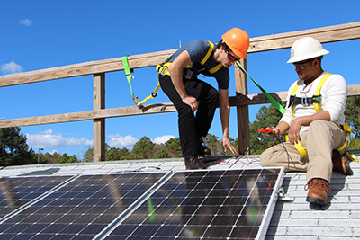 two people install solar panels on a roof