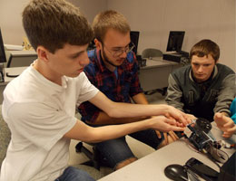 Three TCC engineering students work on building a robot.