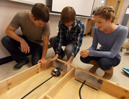 Three TCC engineering students start their robot on a wooden track.