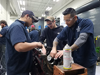 three students work on a diesel engine