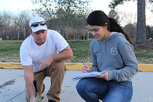 two land surveying students work together on measuring and recording