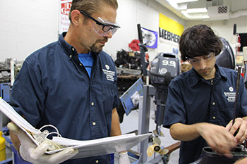 Two students work together in a marine maintenance mechanics class.