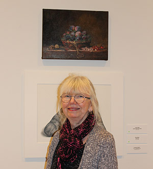 Carolyn Riley posing in front of her painting