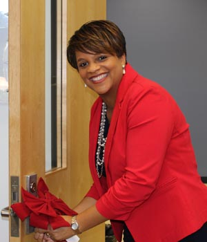 Center for Military and Veteran Education's Tiffanny Putman hangs a bow on the door of the new lounge