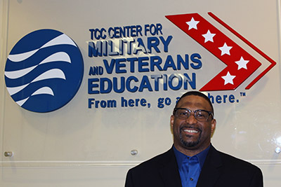 Smiling man standing in front of the logo for TCC's Center for Military and Veterans Education