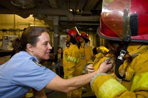 Female firefighter checks the gear of another woman