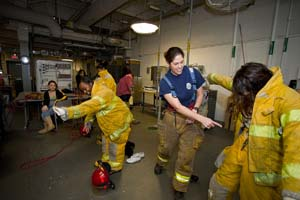 Women put on firefighter gear