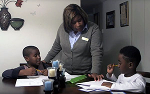 Mother helping two young boys with homework at a table