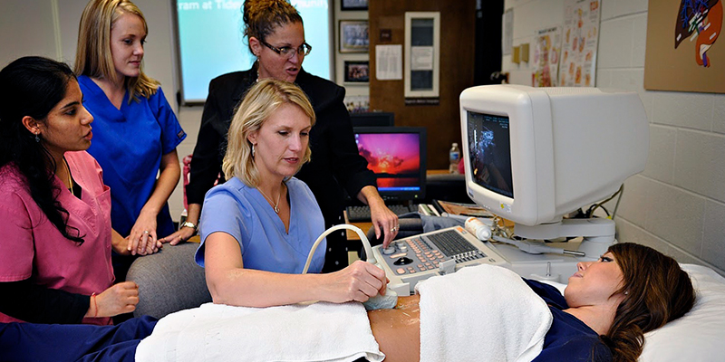 Students providing a free ultrasound to a mom to be.